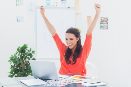 Photo for Excited woman raising her arms while working on her laptop in her office - Royalty Free Image