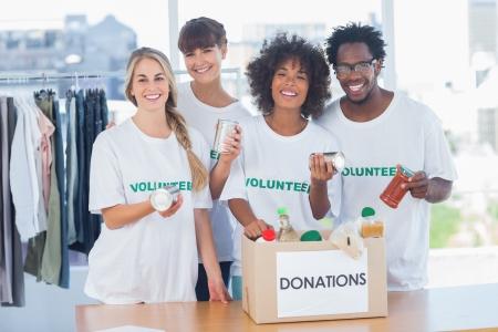 Foto de Volunteers taking out food from a donation box in their office - Imagen libre de derechos