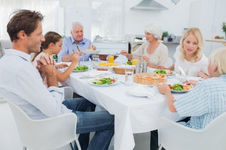 Foto de Extended family at the dinner table in kitchen - Imagen libre de derechos