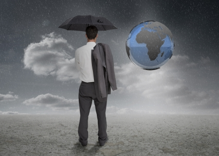 Businessman looking at earth projection and holding his umbrella and jacket