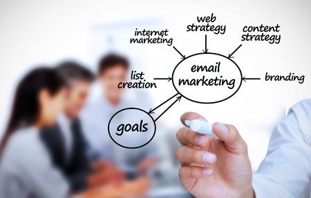 Foto de Businessman writing e-marketing terms in front of a business team - Imagen libre de derechos