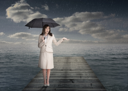 Elegant businesswoman holding an umbrella in front of the sea