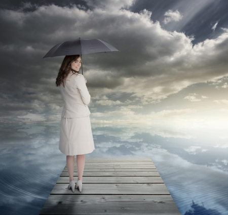 Businesswoman standing on bridge and holding an umbrella