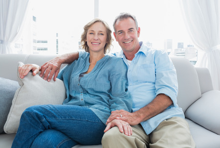 Foto de Middle aged couple relaxing on the couch smiling at camera at home in the living room - Imagen libre de derechos
