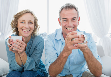 Foto de Smiling middle aged couple sitting on the couch having coffee looking at camera at home in the living room - Imagen libre de derechos