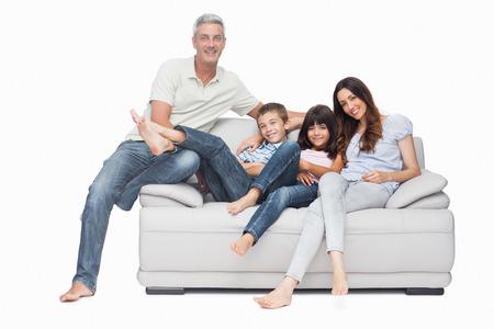 Foto de Family sitting on sofa smiling at camera on white background - Imagen libre de derechos