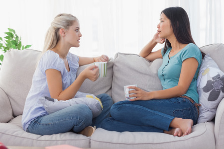 Friends drinking coffee and having a serious chat at home on the couch