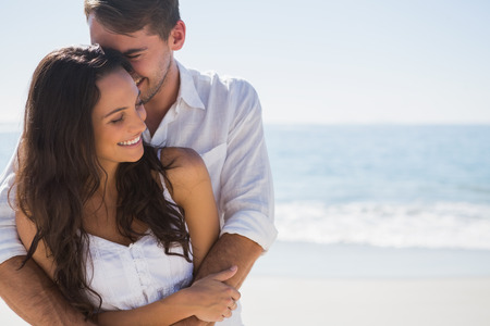 Photo for Attractive couple cuddling at the beach - Royalty Free Image