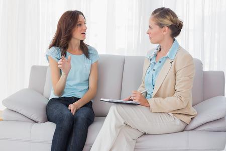 Foto de Woman talking to her psychologist  and sitting on the couch - Imagen libre de derechos