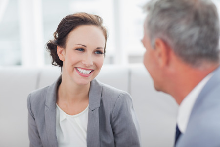 Foto de Cheerful businesswoman listening to her workmate talking in bright office - Imagen libre de derechos