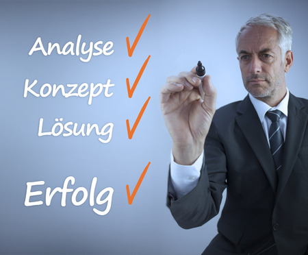 Attractive businessman writing a success checklist in german on grey background