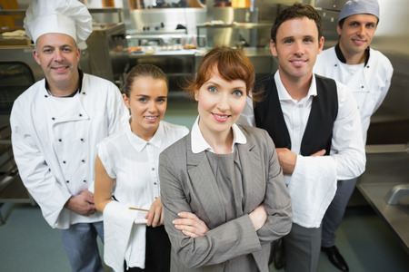 Foto de Cute female manager posing with the staff in a modern kitchen - Imagen libre de derechos