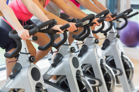 Photo for Mid section of four people working out at spinning class in gym - Royalty Free Image