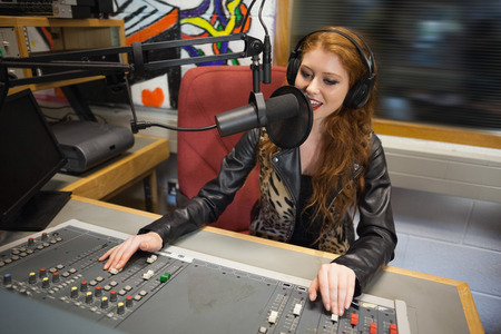 Photo for Happy beautiful radio host moderating sitting in studio at college - Royalty Free Image