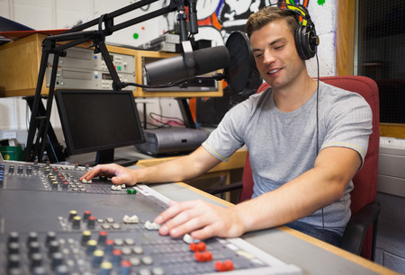 Photo for Handsome happy radio host moderating in studio at college - Royalty Free Image