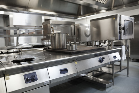 Foto de Picture of fully equipped professional kitchen in bright light - Imagen libre de derechos