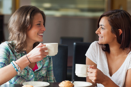 Photo for Two smiling students having a cup of coffee in college canteen - Royalty Free Image