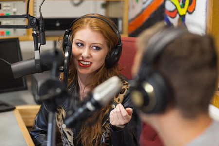 Photo for Attractive happy radio host interviewing a guest in studio at college - Royalty Free Image
