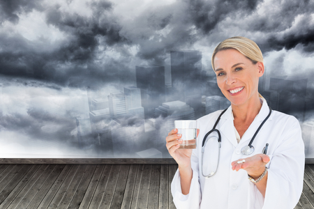 Foto de Composite image of happy doctor holding out pills and water glass - Imagen libre de derechos
