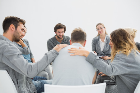 Foto de Group therapy in session sitting in a circle with therapist - Imagen libre de derechos