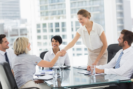 Photo for Side view of executives shaking hands during a business meeting in the office - Royalty Free Image