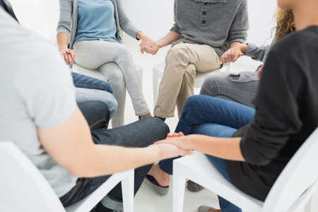 Photo pour Group therapy in session sitting in a circle with therapist - image libre de droit