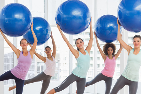 Photo for Happy fitness class and instructor doing pilates exercise with fitness balls in bright room - Royalty Free Image