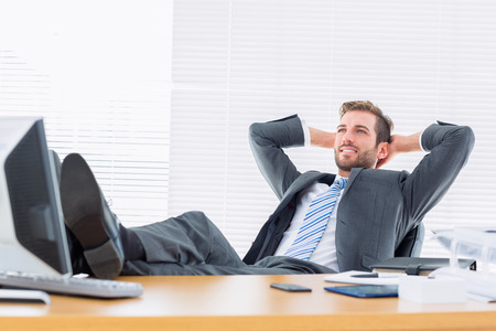 Photo pour Full length of a relaxed confident young businessman sitting with legs on desk at office - image libre de droit