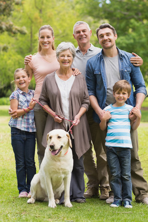 Foto de Portrait of an extended family with their pet dog standing at the park - Imagen libre de derechos