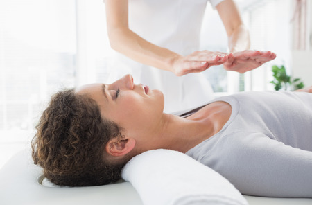 Foto de Attractive young woman having reiki treatment in health spa - Imagen libre de derechos