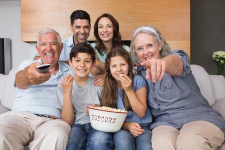 Foto de Portrait of happy extended family watching tv on sofa in the living room at home - Imagen libre de derechos