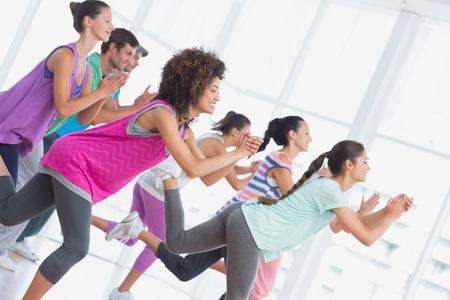 Foto de Fitness class and instructor doing pilates exercise in a bright room - Imagen libre de derechos