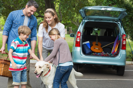 Photo pour Portrait of a happy family of four with pet dog at picnic - image libre de droit