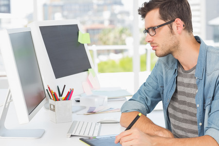 Photo for Side view of a casual male photo editor using graphics tablet in a bright office - Royalty Free Image