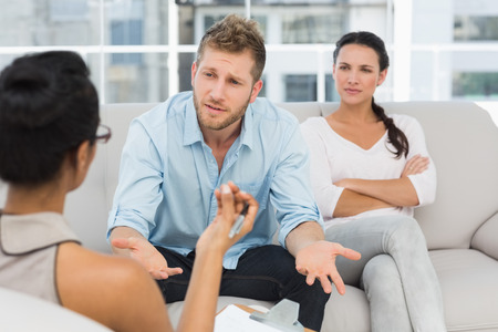 Unhappy couple at therapy session with man talking to therapist in therapists office