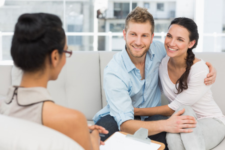 Foto de Smiling couple reconciling at therapy session in therapists office - Imagen libre de derechos