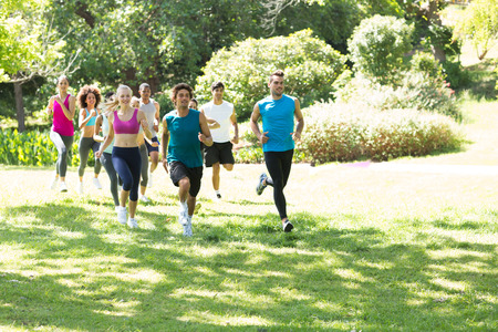 Photo for Group of athletes running on grassy land in park - Royalty Free Image