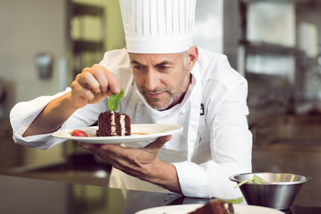 Photo for Closeup of a concentrated male pastry chef decorating dessert in the kitchen - Royalty Free Image