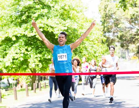 Photo pour Excited male runner crossing the finshline of a marathon - image libre de droit