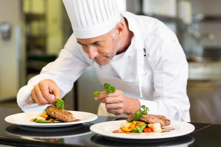 Foto de Closeup of a concentrated male chef garnishing food in the kitchen - Imagen libre de derechos