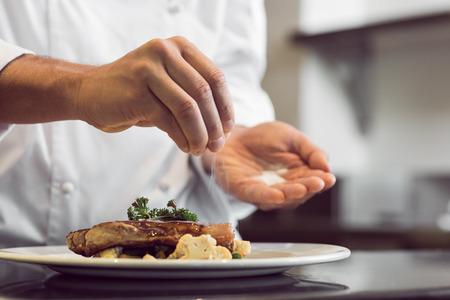 Photo pour Closeup mid section of a chef putting salt in the kitchen - image libre de droit