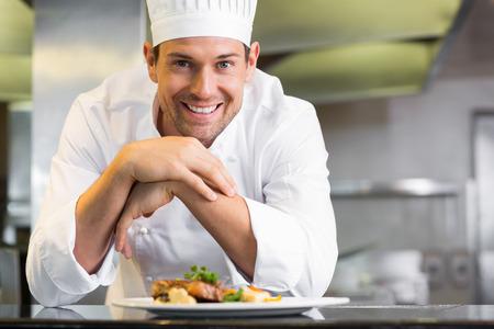 Foto de Portrait of a smiling male chef with cooked food standing in the kitchen - Imagen libre de derechos