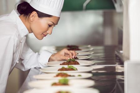 Foto de Side view of a concentrated female chef garnishing food in the kitchen - Imagen libre de derechos