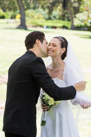 Young romantic groom kissing bride in garden