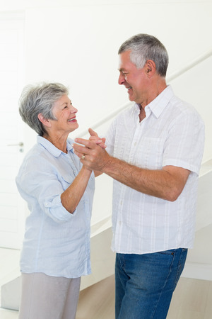 Happy senior couple dancing together at home in living room
