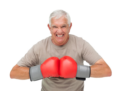 Photo pour Close-up portrait of a determined senior boxer over white background - image libre de droit