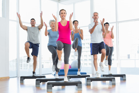 Photo pour Portrait of smiling people doing power fitness exercise at yoga class in fitness studio - image libre de droit