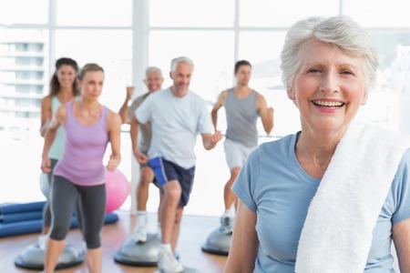 Foto de Portrait of a cheerful senior woman with people exercising in the background at fitness studio - Imagen libre de derechos