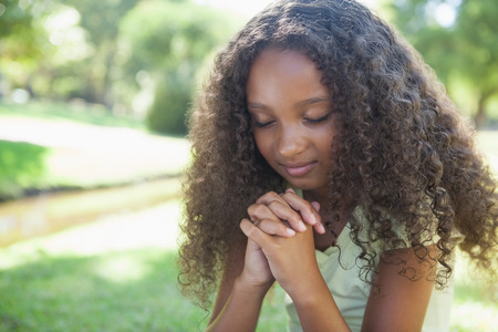 Photo for Young girl praying in the park on a sunny day - Royalty Free Image
