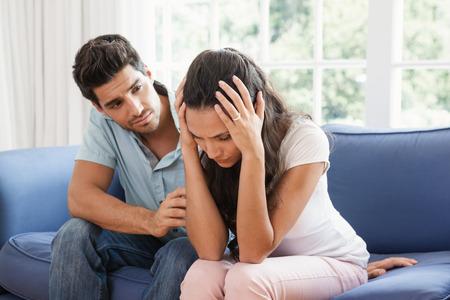 Foto de Man comforting his upset partner at home in living room - Imagen libre de derechos